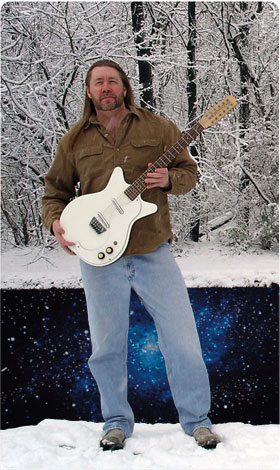 Monty Milne standing in the snow holding a white guitar.
